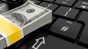 Pengar som ligger på datortangentbordet Arkivbilder