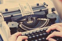 Pengar som skrivas ut i en manuell skrivmaskin som symbol av inflat arkivfoto