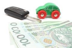Pengar, trägrön leksakbil och tangentmedel Vit bakgrund Arkivfoton