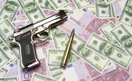 Pengar, vapen och kulor Royaltyfri Bild