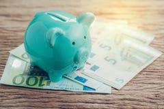 Pengarbesparingar finansiellt konto, begrepp för Europa nationalekonomi, blå spargris på högen av eurosedlar på trätabellen, fram royaltyfria foton