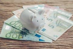 Pengarbesparingar finansiellt konto, begrepp för Europa nationalekonomi, vit spargris på högen av eurosedlar på trätabellen, fram arkivfoto
