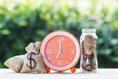 Pengarbesparingar, investering, tid och växande begrepp för pengar: Stapla växande mynt, Moneybags och den orange klockan på trät royaltyfri fotografi