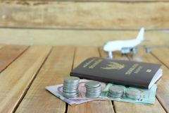 Pengarbesparingbegrepp för semester med myntbunten, passet och flygplanleksaken på träbakgrunderna fotografering för bildbyråer