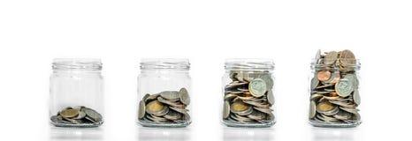 Pengarbesparingen, den glass kruset ordnar med mynt inom att växa, på vit bakgrund arkivbilder