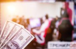 Pengardollar mot bakgrunden av en TV, som e-sportar visas på, sportar som slå vad, pengardollar arkivfoto