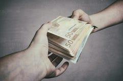 Pengarlån Banktjänsteman som lånar ut bunten av eurosedelpengar Arkivbild