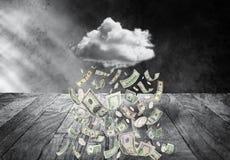 Pengarmoln som regnar pengar arkivfoto