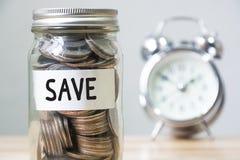 Pengarmyntet i krus med klocka- och texträddningen, begrepp sparar pengar a Royaltyfri Fotografi