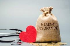 Pengarpåse med mynt och inskriftsjukförsäkringen och en hjärta med en stetoskop Begreppet av medicinsk försäkring av liv arkivbild