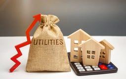 Pengarpåse med ordhjälpmedlen och en övre pil och hus på en räknemaskin Begreppet av att lyfta priser för bruket av arkivbilder