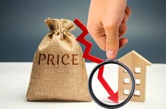 Pengarpåse med ordpris, ner pil och trähus Begreppet av fallande egenskapspriser Lägre inhysa priser Låg hyra royaltyfri foto