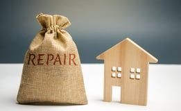 Pengarpåse med ordreparationen och ett trähus Besparing och ackumulation av pengar som ska repareras Begrepp av ett nytt hus, läg arkivbild