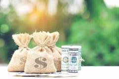 Pengarpåse med sedeln på naturlig grön bakgrund som sparar för arkivbilder