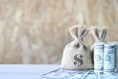 Pengarpåsen med sedeln på träbakgrund som sparar för, förbereder sig fotografering för bildbyråer