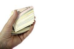 Pengarrulle i hand på en vit bakgrund Arkivfoton