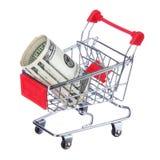 Pengarrulle i shoppingvagnen som isoleras på vit. Dollarräkningar i spårvagn Arkivbild