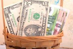 Pengaruppsättning i en korg, dollar, euro Arkivbilder