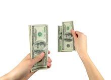 PengarUS dollar i händerna arkivfoton