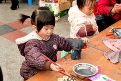 Pengshou, China: Little Girl Painting Figurine Royalty Free Stock Photos