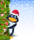 Penguin  behind christmas tree Stock Photo