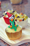 Penguin Christmas Cupcake with Candied Fruit. Holiday Christmas cupcakes decorated with a penguin and dried candied fruit pieces on a wooden cutting board Stock Images