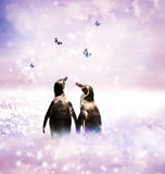Penguin couple in fantasy landscape. Two Penguins holding wings in a fantasy nature landscape with butterflies Stock Photos