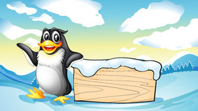 A penguin beside the empty wooden board Stock Images