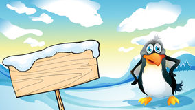 A penguin beside the empty wooden signboard Stock Photo