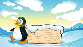 A penguin and an empty wooden template in the snowy area Stock Images