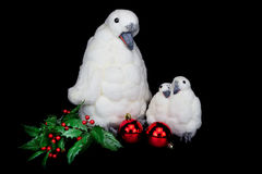 Penguin figurines as family with christmas balls. Penguin figures as family with baubles and holly berries on black background stock images