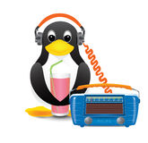 Penguin is listening to music and drinking soda through a straw. Penguin with a glass of lemonade listening to music in headphones Stock Images