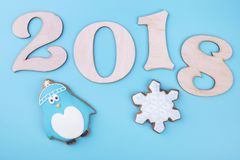 Penguin and snowflake with 2018 figures. Wooden figures and gingerbread. New Year composition on a turquoise background vector illustration