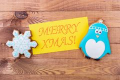 Penguin and a snowflake with an inscription. A gift to a child for Christmas. Gingerbread on a wooden background royalty free stock photography