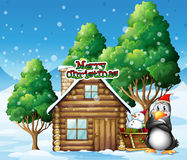 A penguin and a snowman beside the wooden house Royalty Free Stock Photos