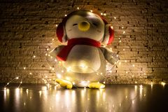 Penguin toy surrounded by garland with decorated wall background. photo in dark. stock image