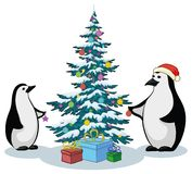 Penguins and Christmas tree. Antarctic emperor penguins decorate the Christmas tree Stock Photo