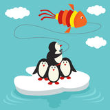 Penguins on ice floe launch a kite in form of fish Royalty Free Stock Photo