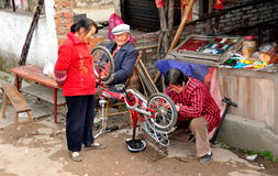Pengzhou, Китай: Женщина ремонтируя велосипед Стоковая Фотография