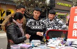 Pengzhou, China: Adolescencias que venden las cubiertas del teléfono móvil Fotografía de archivo libre de regalías