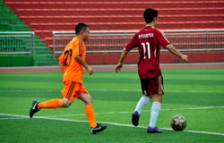 Pengzhou, China: Athletes Playing Football. Two Chinese athletes playing soccer on the Astroturf field in Pengzhou Stadium in Pengzhou City, China Royalty Free Stock Photo