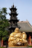 Pengzhou, China: Buddha at Long Xing Temple. A large smiling gilded Buddha and five tiered incense brazier tower in a courtyard at the Long Xing temple in Royalty Free Stock Photos