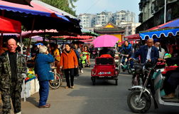 Pengzhou, China: Bustling Long Xing Marketplace. The busy outdoor Long Xing marketplace bustles with vendors, shoppers, and vehicles in Pengzhou, China Royalty Free Stock Images