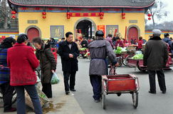 Pengzhou, China: Busy Long Xing Square. Customers and vendors in the busy outdoor marketplace in front of the Long Xing Temple hung with red lanterns in Pengzhou Royalty Free Stock Images