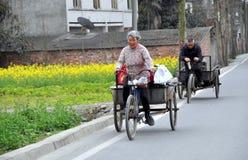 Pengzhou, China: Carros de la bicicleta del montar a caballo del hombre y de la esposa Imagen de archivo