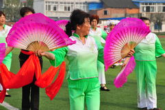 Pengzhou, China: Chinese Dance Group. Woman with two pink fans performing a traditional Chinese dance routine at Pengzhou stadium in Pengzhou, China Royalty Free Stock Photo