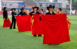 Pengzhou, China: Chinese Flamenco Dancers. A group of dancers in colourful red and yellow Flamenco costumes rehearsing a routine on the Astroturf in Pengzhou Royalty Free Stock Photography