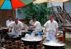 Pengzhou, China: Cocineros con los Woks imagen de archivo libre de regalías