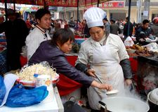 Pengzhou, China: Cooks at Food Festival. The owner of a food booth checks noodles boiling in a large steel pot for correct degree of doneness with her chef at Royalty Free Stock Photography