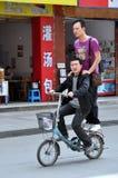 Pengzhou, China: Dois homens em uma bicicleta foto de stock royalty free
